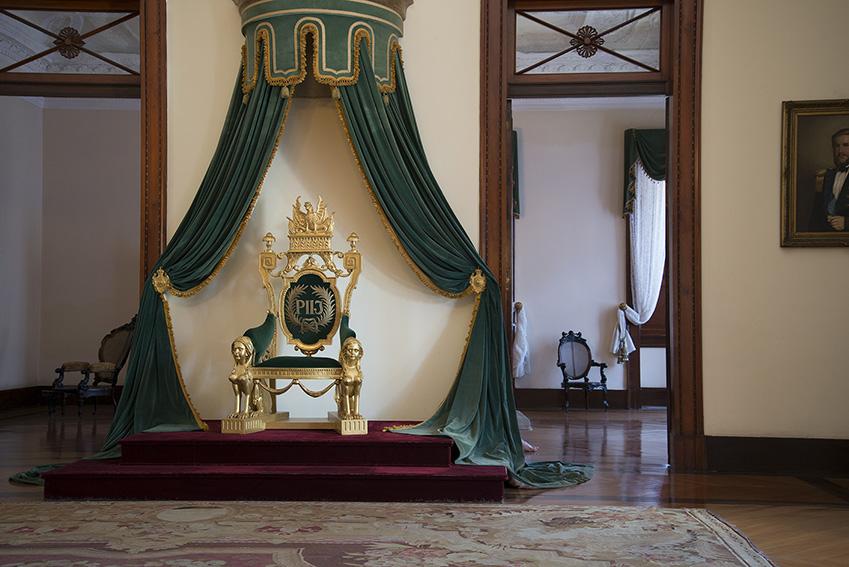 Sala de estado, trono em talha dourada e forro de veludo verde, no encosto, entre duas palmas, a sigla P II I (Pedro Segundo Imperador) bordada a prata, pés dianteiros constituídos por duas esfinges, Ada, tapete Aubusson com a marca CJ Sallandrouze (1852). Museu Imperial/Ibram/MinC/2015
